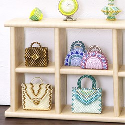 Miniature beaded bags displayed on a small shelf