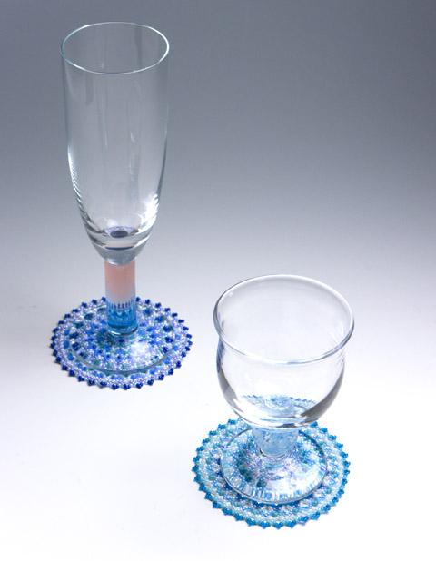 小さな円形のビーズのドイリーマットの上にグラスを置く。