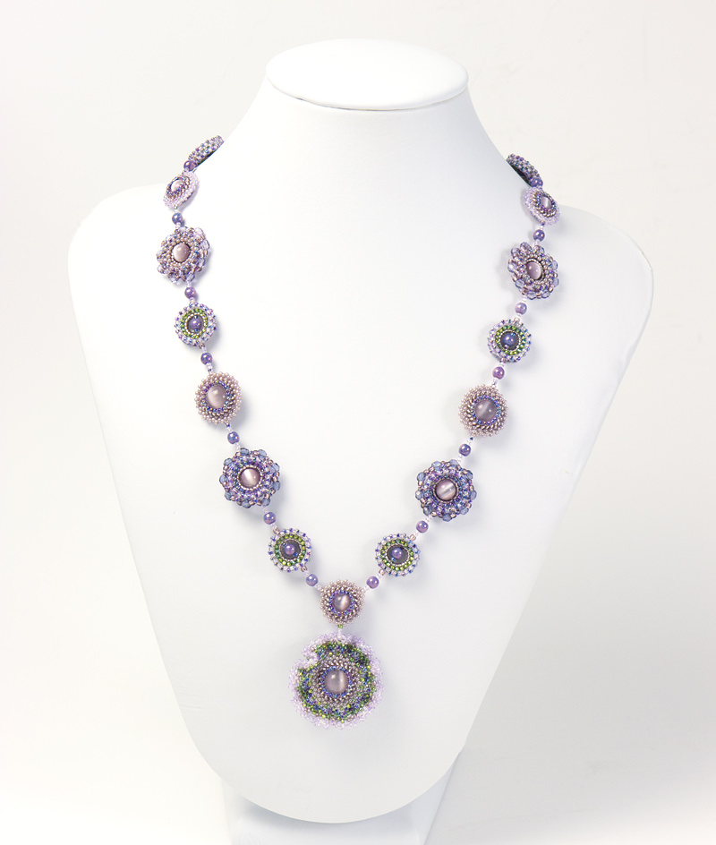 Frilly Flowers Necklace is displayed on a jewelry display stand.