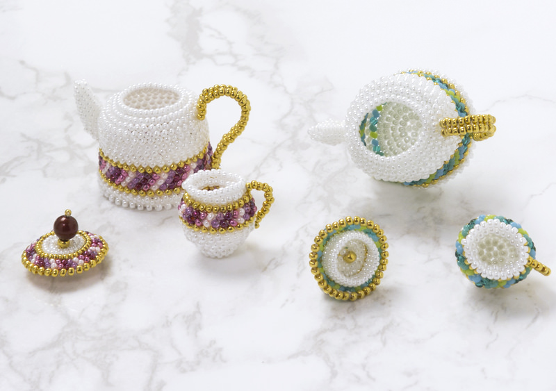 The lid of the beaded teapot can be opened.